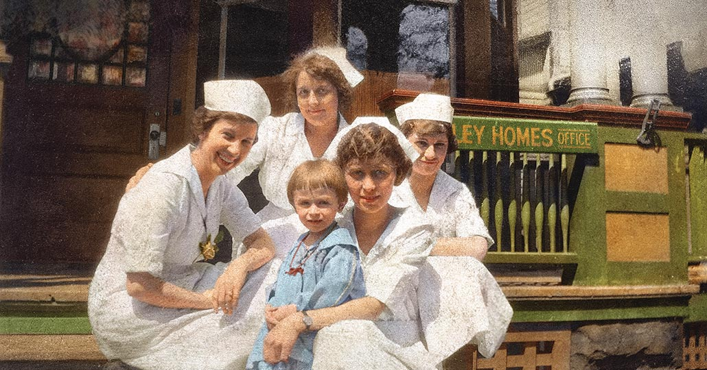 Four female nurses wearing white uniforms with a small child in the middle, looking at the camera