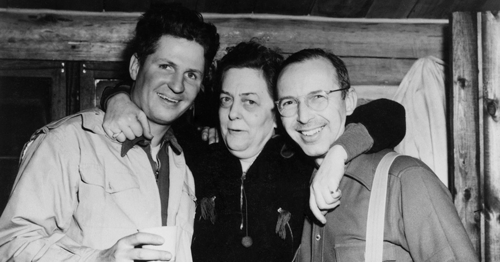 black and white image of two men and a woman with her arms around the two men
