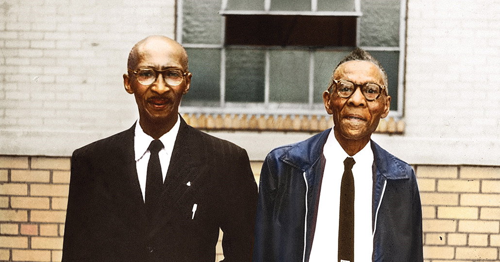 two older man of color, standing side by side. one wearing a suit and tie, the other where a leather jacket and tie.