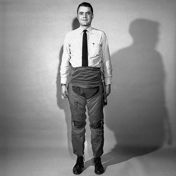black and white image of a man wearing a white shirt and black tie, in baggy pants