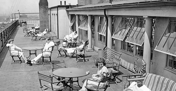 black and white photo of men and women sitting on a rooftop patio