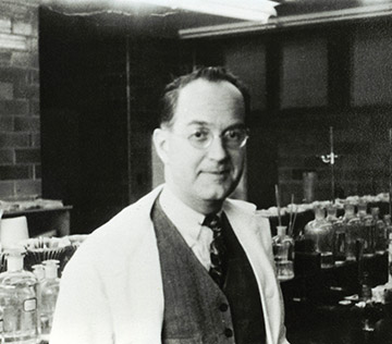 Dr. Irvine Page posing for a photo in front of his lab