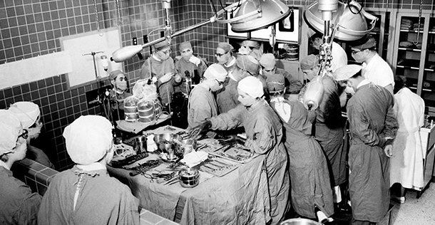 black and white image of multiple doctors in a surgery wearing surgical scrubs