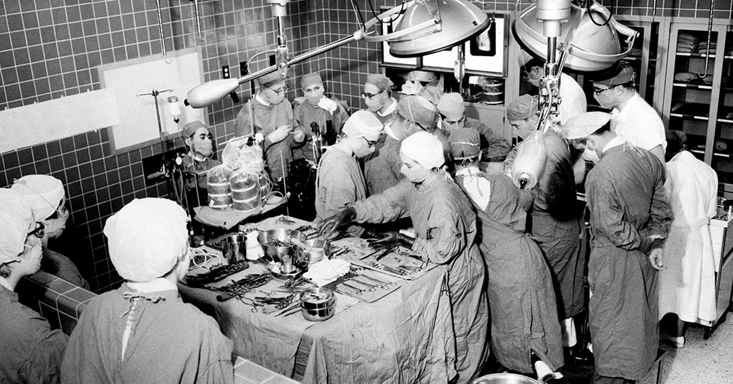 black and white image of multiple doctors in a surgery wearing surgical scruba