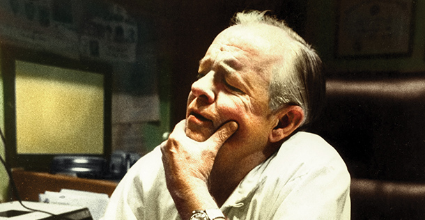 Dr. F. Mason Sones sitting at a desk with his hand on his chin, looking out of frame.