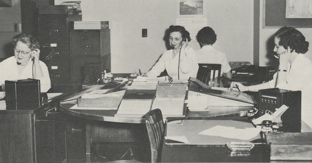 Image of 4 woman with telephones to their ears, sitting at desks