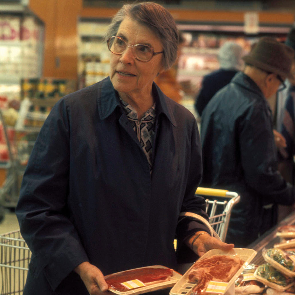 Helen Brown, PhD standing in a grocery store, holding two packages of red meat, looking out of frame