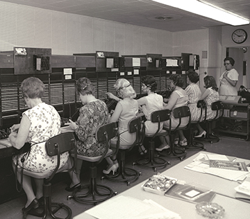 8 women, 7 who are sitting at the phone operator's table, connecting lines