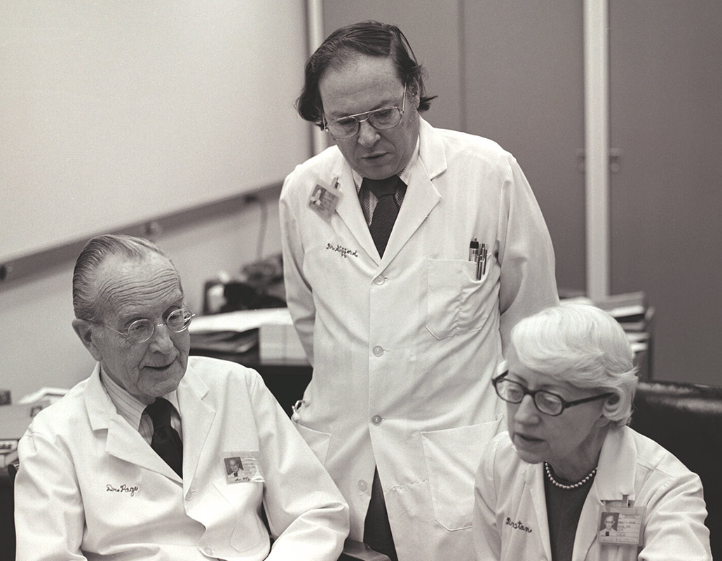 Drs. Page, Gifford and Dustan looking at paperwork on a table