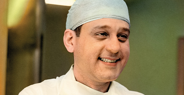 Dr. Rene smiling, looking out of frame, wearing a medical cap and uniform