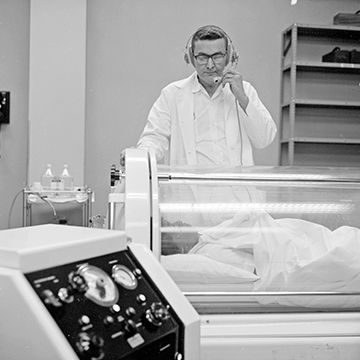 Dr. Wasmuth at a hyperbaric oxygen chamber with a patient inside, speaking into a headset. Centennial-ThinkingBig-Floated