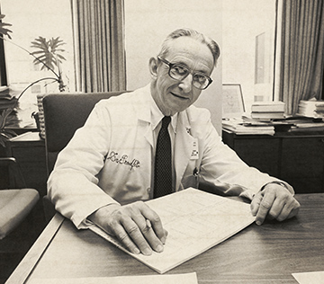 William Proudfit, MD., sitting at this desk with paper on the tabletop, looking at the camera