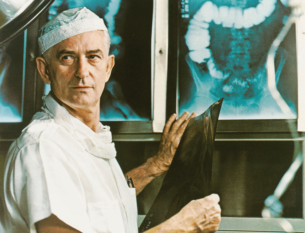 Rupert Turnball, MD. holding an x-ray image of an organ, looking out of frame.