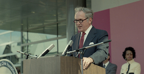 Dr. William Kiser standing behind a podium, speaking into a microphone.
