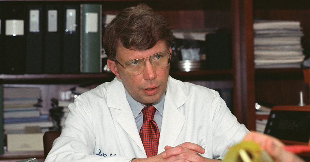 Dr. Floyd Loop sitting behind his desk looking at someone out of frame.