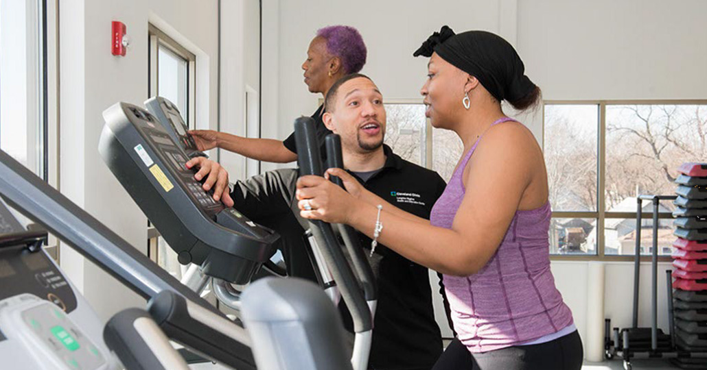 3 people at a gym, a male is training a female on an elliptical