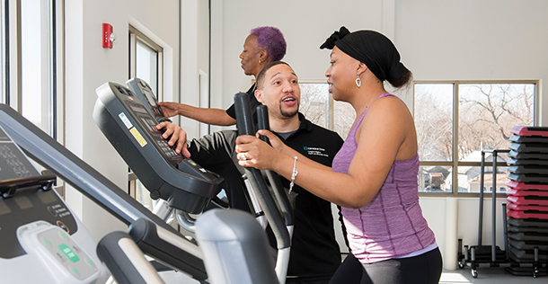 a male trainer working with a woman on a treadmill