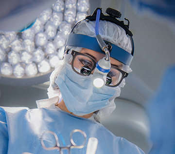 female doctors wearing medical gear, glasses and a light on her head