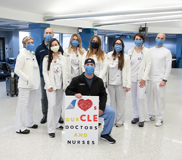 group of medical professionals posing with a poster in the Cleveland airport