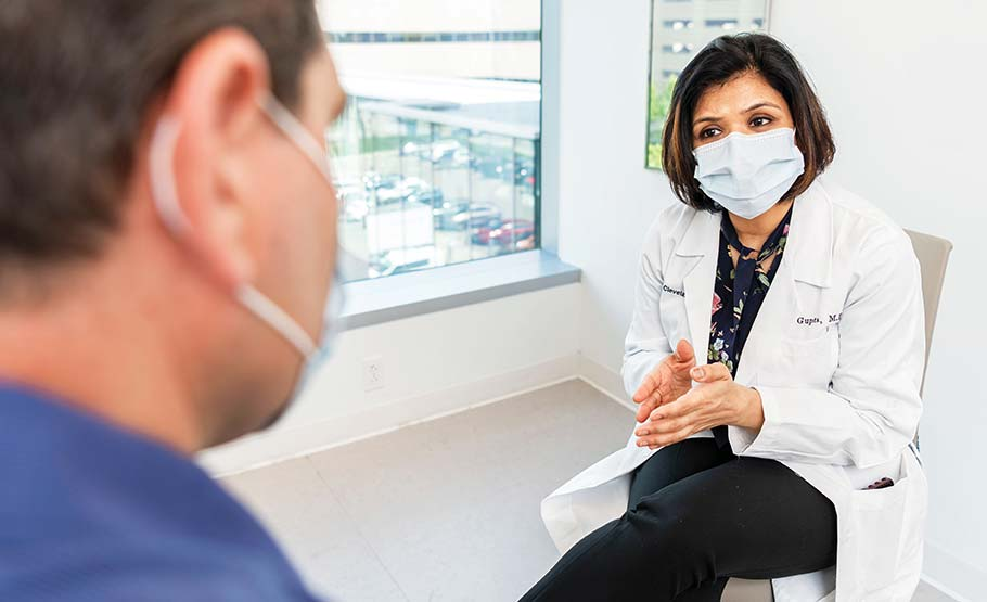 Female doctor in white lab coat, seated, talking to a man. both wearing face masks.