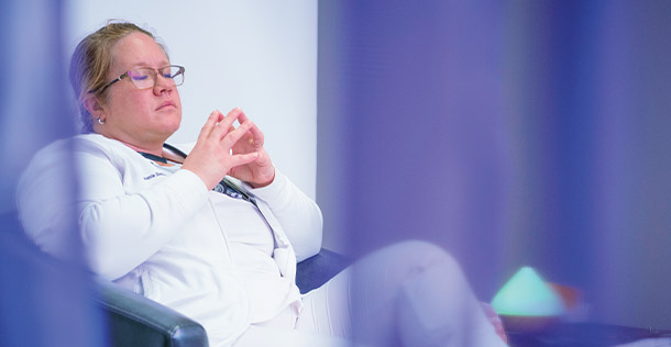 Doctor behind a purple curtain, sitting in chair with her eyes closed,