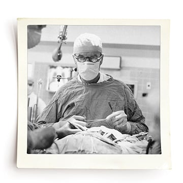Black and white photo of doctor in an operating room holding medical tools. He is wearing a scrub cap, face mask, glasses and a surgical cape.
