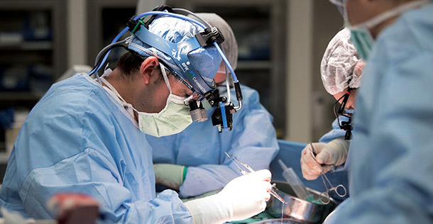 Doctor in blue surgical gear, wearing medical head gear to operate on patient