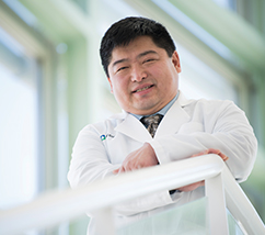 Dr. Timothy Chan posing for a photograph with his armed crossed