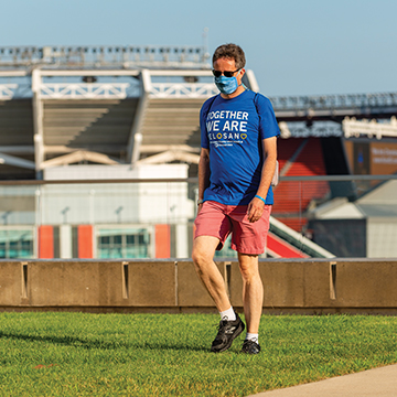 Man wearing blue VeloSano shirt, a face mask and pink shorts, walking outside of First Energy stadium