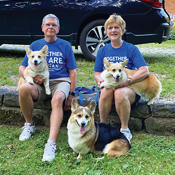 A man and a woman sitting outside, both holding a corgi, and another corgi is sitting in the grass in between them