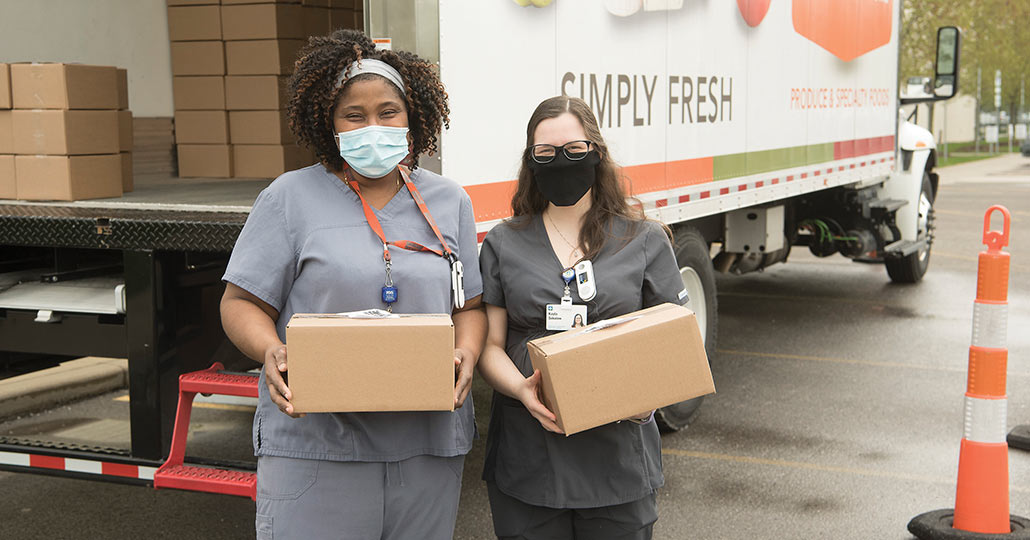 Two female doctors wearing face masks, standing outside holding packages