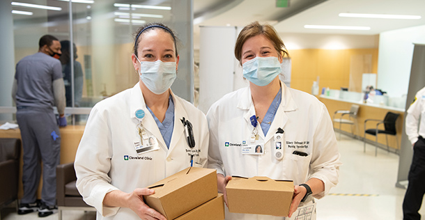 Two female caregivers wearing surgical masks and white lab coats holding brown rectangular take out containers