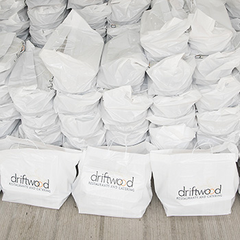 Stacks of white takeout bags with a driftwood logo printed on front