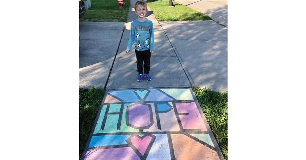 Young Boy standing in front of chalk drawing that says hope