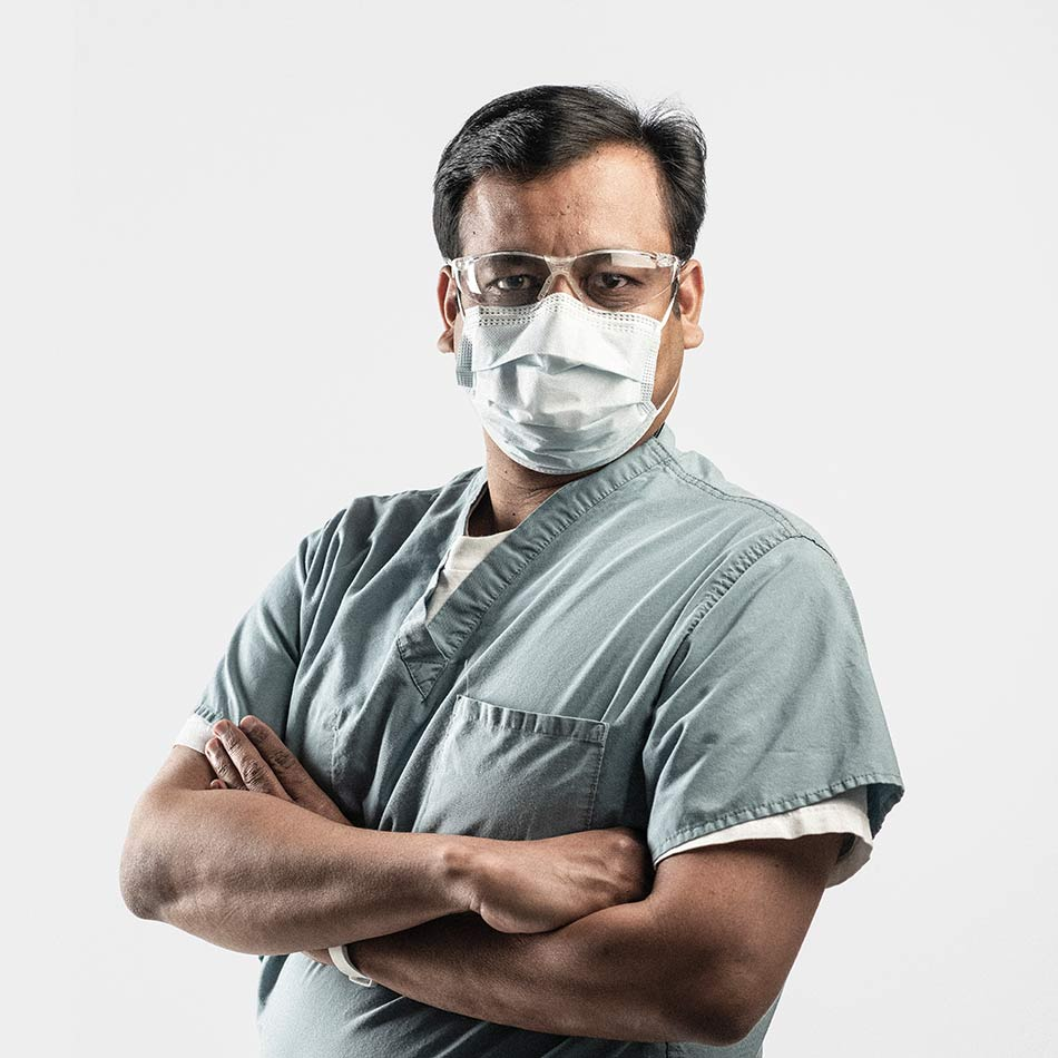 Debasis Sahoo posing for photo with arms crossed wearing a face mask