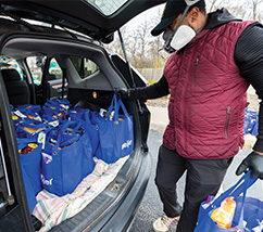 Guy wearing a winter vest and face mask, putting blue bags full of groceries into trunk of car