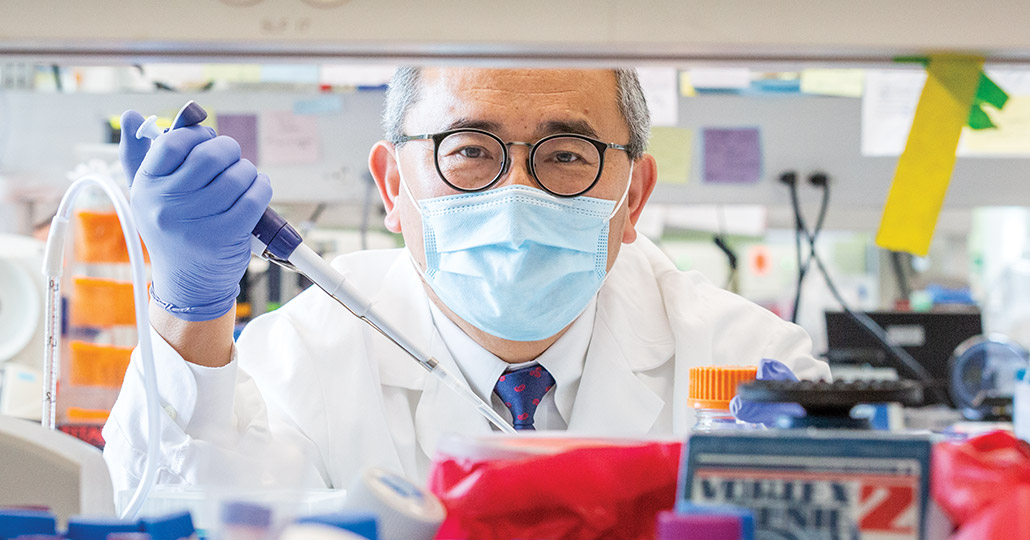Doctor wearing glasses and a face mask holding a testing tool, shown between shelves holding medical supplies.