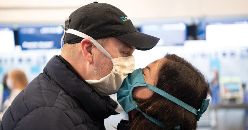 Masked couple kissing