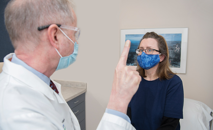 A male doctor wearing a surgical mask, waving his finger in the air while the patient across from him looks at it.