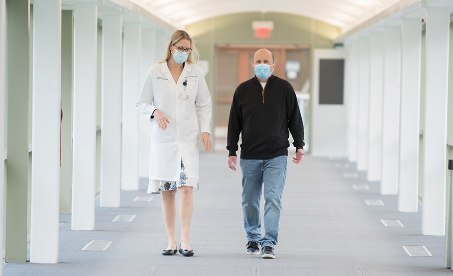A female doctors and a male patient wearing surgical face masks, walking in a corridor