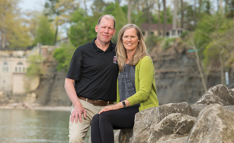 Kevin Kelley and his wife posing for a photo on a rock with a pond behind them