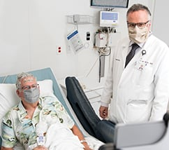 Dr. Najm wearing a face mask standing next to a patient with who is lying in a hospital bed, wearing a face mask with wires on his head.