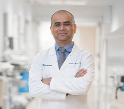 Dr. Saket Saxena, MD, standing with his arms crossed in a hospital