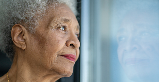 Older woman looking out of a window, her reflection appears in the glass of the window
