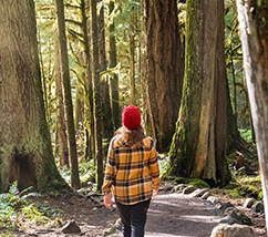 Woman wearing a red beanie and a yellow flannel and black pants, walking a trail in the middle of the woods