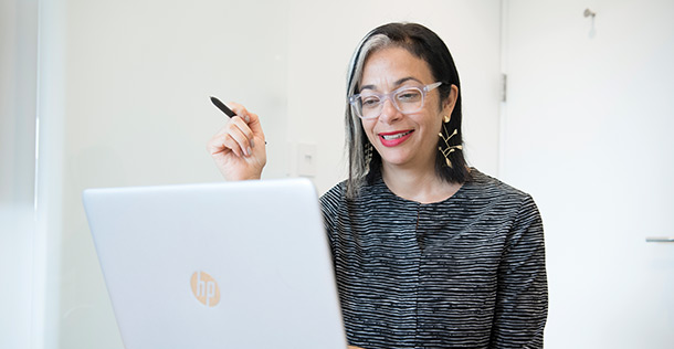 Lara wearing a black and white striped shirt, holding a pen, sitting behind a laptop, smiling
