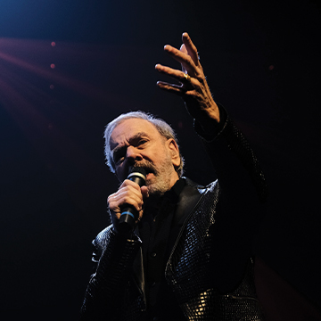Neil Diamond wearing a black shiny blazer, raising his left hand to the sky while holding a microphone in the other, singing