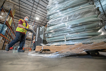 A male worker wearing a safety vest and mask, pushing a pallet lift of medical supplies in a warehouse