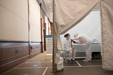 Two nurses in a white tent. One administering a shot into the other nurse who is sitting in a chair.