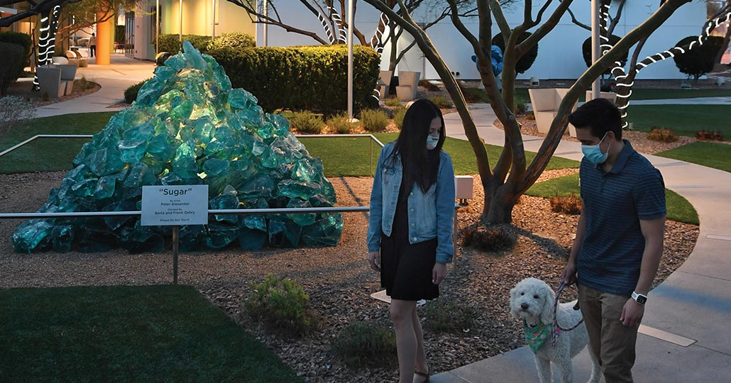 A man and a woman walking a dog in a park with a turquoise glass pyramid sculpture in the background